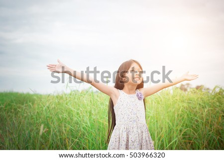 Little cute asian girl standing among the purple flower field sunshine day. Freedom enjoying with nature.
