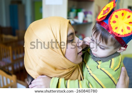 Little cute baby boy hugging and kissing his mother - stock photo