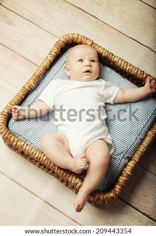 little cute baby boy  lying in basket  - stock photo