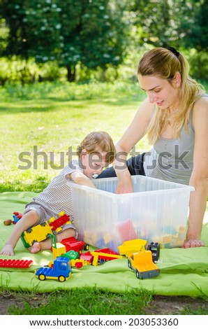Little cute baby boy plays toys with young beautiful mother in the park
