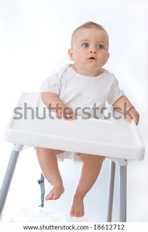 little, cute baby boy sitting in high chair, on white - stock photo