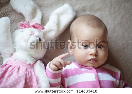Little cute baby girl and rabbit mascot - stock photo