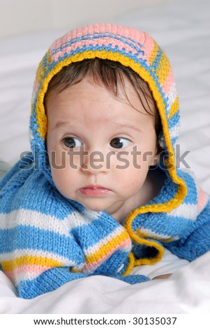 little cute baby girl in blue knitted jumper