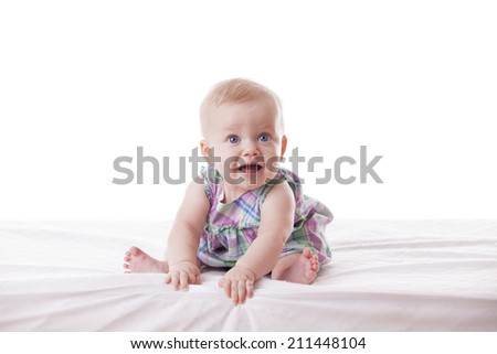 Little cute baby-girl in dress, sitting, isolated