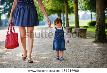Little cute baby girl walking with beautiful mother in summer park - stock photo