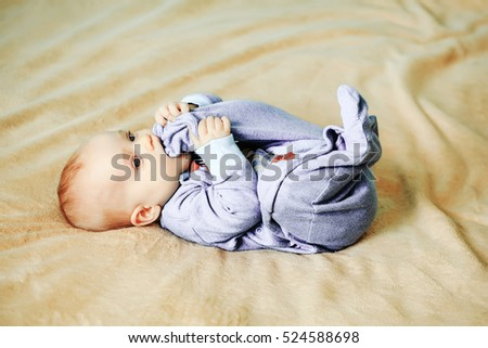 Little cute baby in adorable blue bomber bites his foot on bed