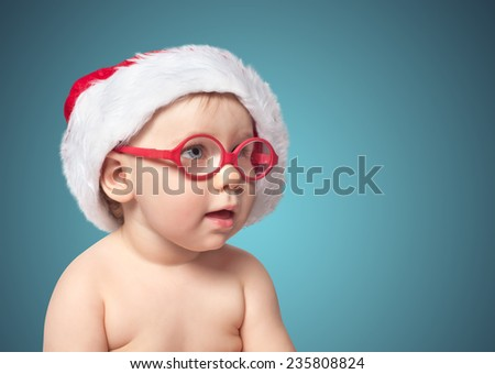 little cute baby in red Santa hat on color bacground. close up portrait - stock photo