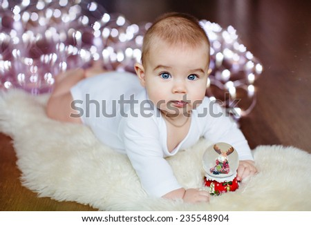 Little cute baby lying on the floor on the background lights near the Christmas ball - stock photo