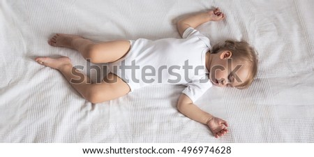 Little, cute baby sleeping in hiscrib. Peaceful baby lying on a bed while sleeping in a bright room.