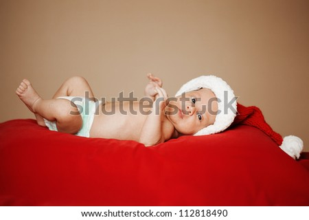 little cute baby with santa hat on red background - stock photo