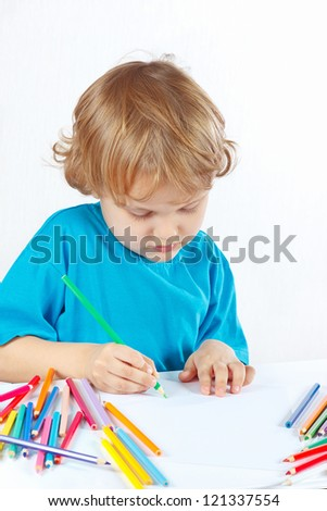 Little cute blond boy draws with color pencils on a white background