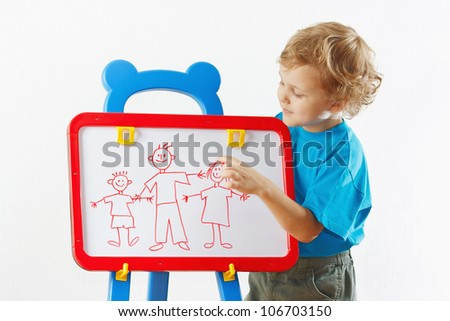 Little cute blond boy shows his family painted on a whiteboard - stock photo
