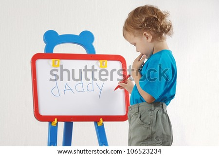 Little cute blond boy wrote the word daddy on whiteboard - stock photo