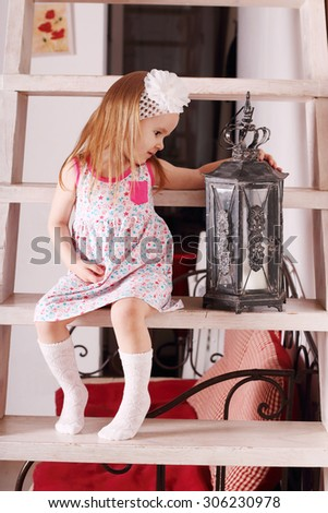 Little cute blond girl in dress sitting on wooden stairs with with old lamp. Focus on lamp