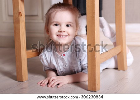Little cute blond girl in striped shirt is smiling on floor under stool