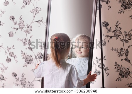 Little cute blond girl in striped shirt looking at his reflection in mirror - stock photo