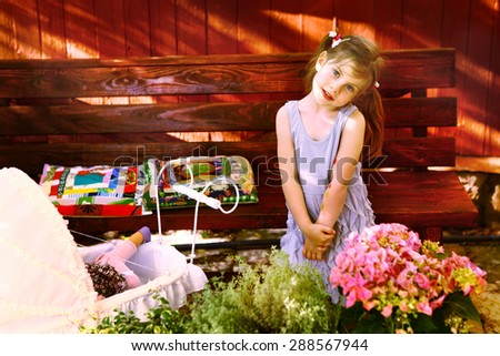 little cute blond girl with pram flowers seat on the wooden bench on the village house background - stock photo