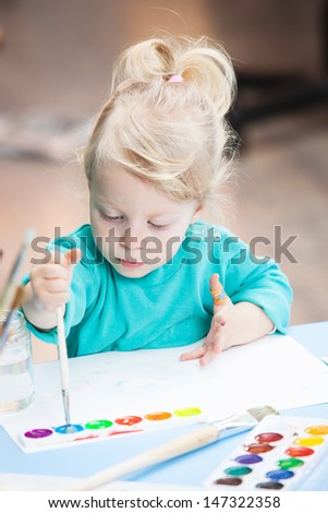 Little cute blonde girl drawing with watercolor paints
