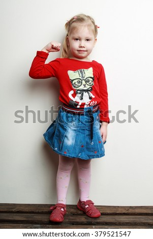 Little cute blonde girl in a red shirt and a jeans skirt is standing near the wall showing the biceps