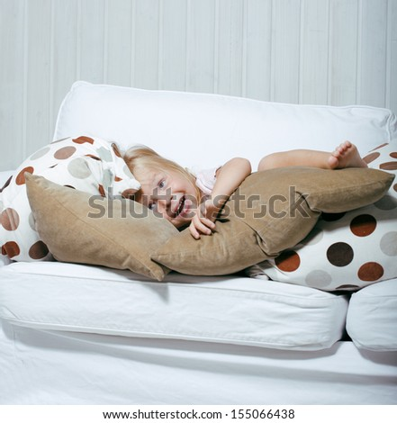 little cute blonde girl playing at home with pillows - stock photo