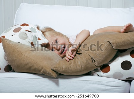 little cute blonde norwegian real girl playing at home with pillows - stock photo