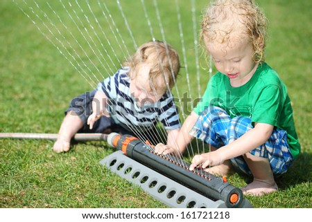 Little cute boy and toddler touch sprinkler in garden at sunny summer day.
