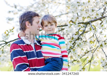 Little cute boy and young father hugging in blooming cherry garden in spring. Happy family celebrating father's day. - stock photo