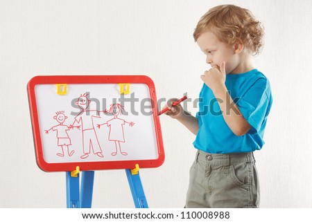 Little cute boy drew a family on a whiteboard - stock photo