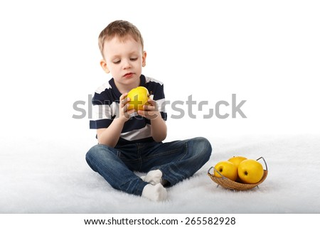 Little cute boy eating a yellow apple and smiling isolated on white background - stock photo