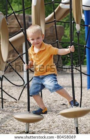 Little cute boy enjoys sunny day at the playground.