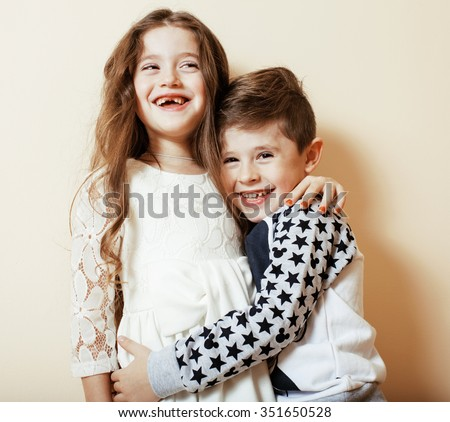 little cute boy girl hugging playing on white background, happy family close up isolated. brother and sister smiling - stock photo