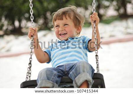 Little cute boy having fun on chain swings. - stock photo