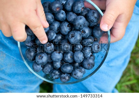 little cute boy holding bowl with blueberries