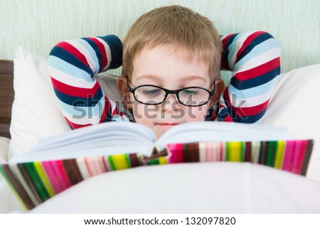 Little cute boy in glasses reading book in bed - stock photo