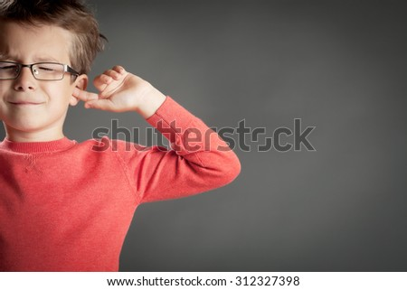 Little cute boy in glasses shutting his ears in denial. Studio shot portrait over gray background. Fashionable little boy. - stock photo