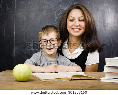 little cute boy in glasses with young real teacher, classroom studying at blackboard - stock photo