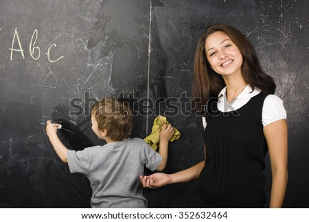 little cute boy in glasses with young real teacher, classroom studying at blackboard, kindergarden senior - stock photo