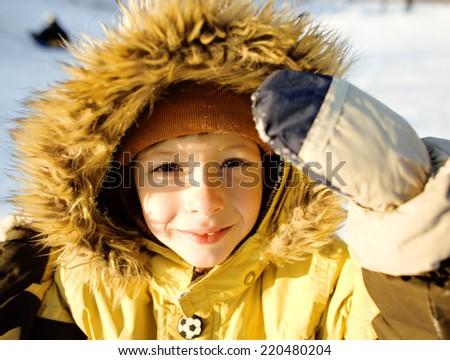 little cute boy in hood with fur on snow outside, sunny smiling - stock photo