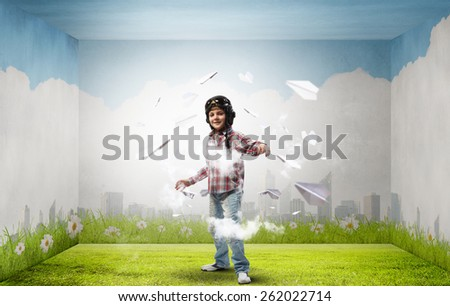 Little cute boy in pilot helmet and paper airplanes flying around - stock photo