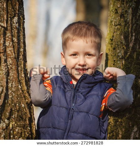 Little cute  boy in stands among the trees in sunny spring day - stock photo