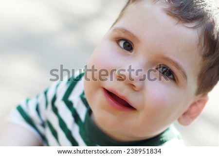 Little cute boy looks up at sunny summer day outdoor. Shallow dof - stock photo