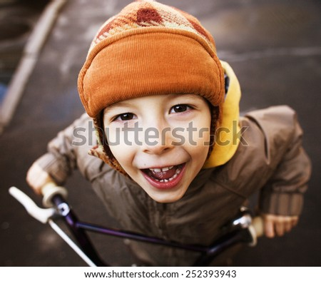 little cute boy on bicycle smiling close up in hat