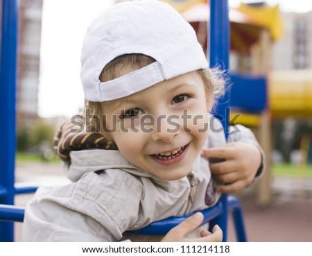 little cute boy on swing outside - stock photo