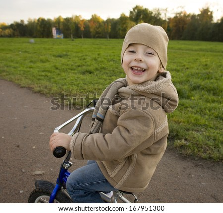 little cute boy outside in park near carousel on bicycle - stock photo
