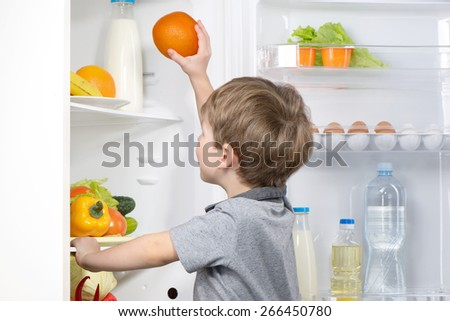 Little cute boy picking orange from fridge. Vegetables and fruits in the refrigerator - stock photo