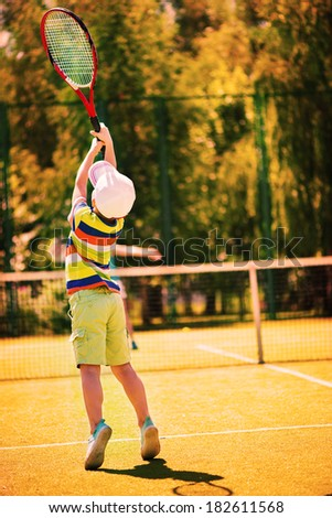 Little cute boy playing tennis on green court - stock photo