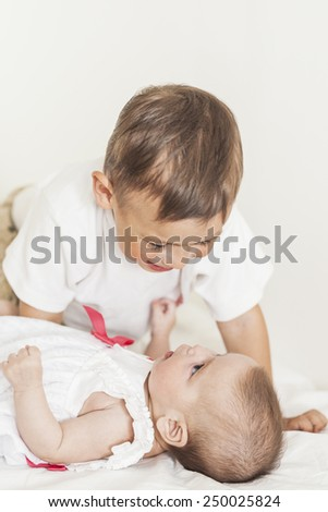 Little Cute Boy Playing with His Infant Sister and Smiling.Against White Background. Vertical Image Composition - stock photo