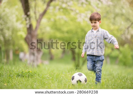 Little cute boy playing with soccer ball in summer park.