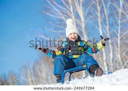 Little cute boy riding sled in winter park - stock photo