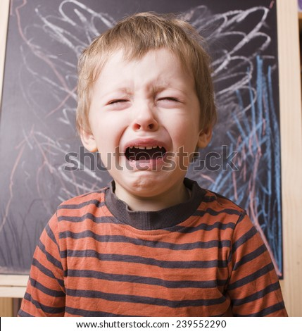 little cute boy screaming and crying at school near blackboard - stock photo
